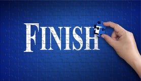 Mot de finition sur le casse-tête Main d'homme tenant un puzzle bleu sur Photos stock