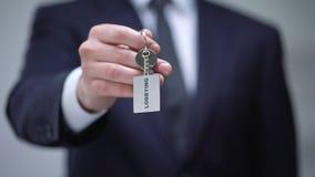 Mot de incitation sur le keychain dans la main d'homme d'affaires, protection illégale d'intérêts banque de vidéos