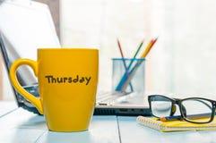 Mot de jeudi écrit sur la tasse de café jaune sur le lieu de travail maorning de bureau avec l'ordinateur portable et les verres Photographie stock