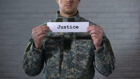 Mot de justice écrit sur des mains de signe dedans du soldat masculin, tribunal militaire, tribunal banque de vidéos