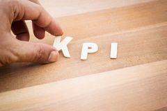 Mot de KPI avec la main masculine sur la table en bois Vente d'affaires, analyse Image stock