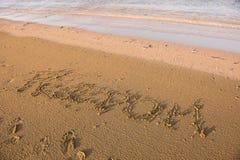 Mot de liberté écrit en sable Image libre de droits
