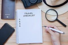 Mot de liste de contrôle de voyage d'écriture de voyageur de main sur le carnet avec les accessoires, la caméra, le téléphone et  photo libre de droits