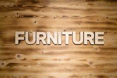 Mot de MEUBLES fait de caractères gras en bois sur le conseil en bois photographie stock