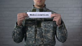 Mot de mobilisation écrit sur les mains masculines de soldat de signe dedans, se préparant à la guerre banque de vidéos