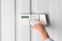 Mot de passe de dactylographie de personne sur l'alarme de sécurité à la maison Images libres de droits