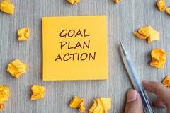 Mot de but, de plan, d'action sur la note jaune avec le stylo de participation d'homme d'affaires et papier emietté sur le fond e images stock