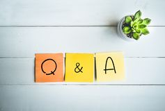 Mot de Q et d'A avec la note de papier sur le fond en bois blanc de table photo stock