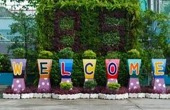 Mot de signe bienvenu sur des pots de fleur Photo stock