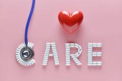 Mot de SOIN fait à partir des pilules de médecine et du stéthoscope, coeur rouge sur le fond rose Concept de jour du ` s de Valen image libre de droits