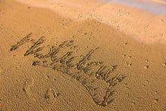 Mot de vacances écrit en sable Photographie stock