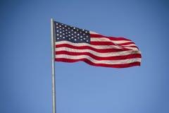 mot den amerikanska skyen för blå flagga Royaltyfri Foto