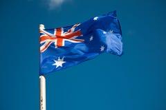 mot den australiensiska skyen för blå flagga Royaltyfri Bild