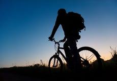 mot den mörka silhouetteskyen för cyklist royaltyfri bild
