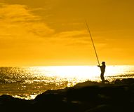 mot den orange silhouetted skyen för fiskare Arkivfoto