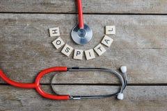 Mot des textes d'hôpital fait avec les blocs en bois et le coeur rouge, stethosco Photos stock