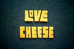 Mot des textes de fromage d'amour sur le fond foncé Découpez le cheddar jaune i Photo stock