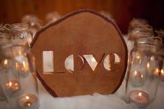 Mot en bois AMOUR sur le tissu blanc autour des bougies brûlantes handmade Photographie stock libre de droits