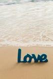 Mot en bois bleu d'amour en sable avec des vagues à la plage Images libres de droits