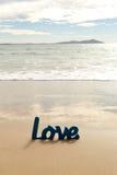 Mot en bois bleu d'amour en sable avec des vagues à la plage Photo stock