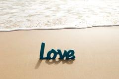 Mot en bois bleu d'amour en sable avec des vagues à la plage Image libre de droits