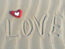 Mot en pierre de coeur et d'amour sur le sable Photos stock