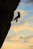 mot för rocksilhouette för klättrare den molniga skyen Arkivfoto