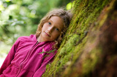 mot flickan som lutar den mossy treen Arkivfoton