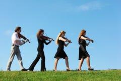 mot fyra går musiker som leker skyfioler Arkivbild