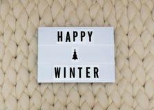 Mot HEUREUX d'HIVER sur le lightbox sur le fond de knit Compozition confortable Tricotez le fond image libre de droits