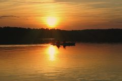 mot kayakerssommarsolnedgång royaltyfri fotografi