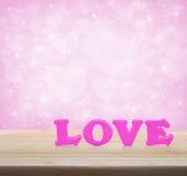 Mot rose d'amour sur la table en bois au-dessus du backgr rose-clair de tache floue de coeur Images libres de droits