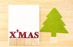 Mot rouge de x'mas et carte postale vide avec l'arbre de Noël vert dans W Photographie stock