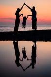 mot silhouettes för nedgångfamiljhav Royaltyfri Fotografi