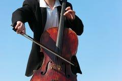 mot tät musiker plays skyen upp violoncelloen royaltyfri bild