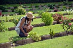 Mot thaïlandais de lecture de femme sur le cimetière de guerre de Kanchanaburi de pierre tombale (Don Rak) Photo stock