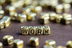 Mot TRAVAIL de motivation fait à partir de petites lettres d'or sur le brun photo libre de droits