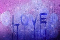 Mot triste d'amour manuscrit sur la fenêtre humide Photo stock