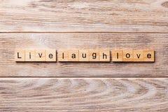 Mot vivant d'amour de rire écrit sur le bloc en bois Texte vivant d'amour de rire sur la table en bois pour votre desing, concept photo stock