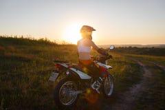 Motard de femme dans le coucher du soleil, moto femelle photo libre de droits