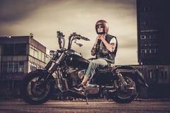 Motard et sa moto de style de bobber Photos libres de droits