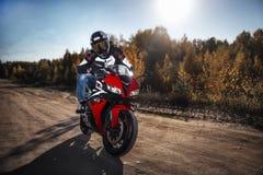 Motard s'asseyant sur une moto près de la ville images libres de droits
