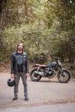 Motard se tenant prêt sa moto de croiseur un jour ensoleillé photographie stock libre de droits