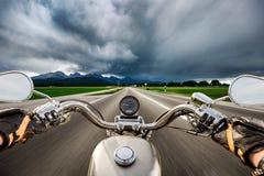 Motard sur une moto dévalant en bas de la route dans un stor de foudre Photographie stock libre de droits