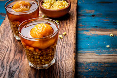 Mote con huesillo. Traditional Chilean drink made from cooked husked wheat and dried peach on wooden board, rustic blue. Background Royalty Free Stock Photos