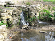 Mote Park waterfall. A small Historic waterfall in Mote Park surrounded by old ragstone slabs Stock Photos