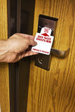 Motel Insert Into Lock Sign. Most motels have do not disturb signs to put on the room doors. A man's hand is removing or putting the sign in the electronic Stock Image