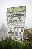 Motel sign with pool Cable TV spa sauna. Outdoor motel sign in the fog with vacancy, pool, spa, sauna and cable TV Royalty Free Stock Image