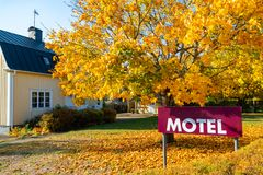 Motel sign with scandinavian house and autumn trees at the background royalty free stock photos