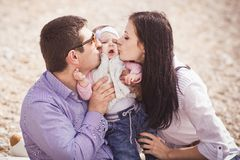 Moter and father kissing little daughter. Happy family - mother, father and little daughter - having fun on the beach Royalty Free Stock Images